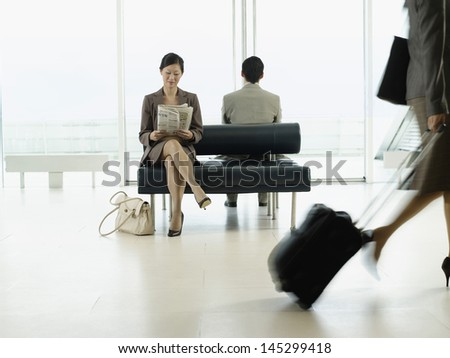 Businesswoman sitting on bench and reading newspaper in airport - stock photo