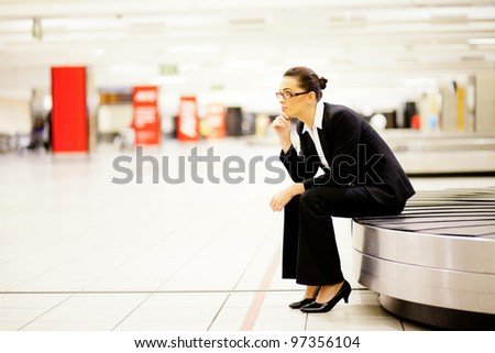 businesswoman sitting on conveyor belt and waiting for her luggage at airport - stock photo