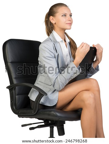 Businesswoman sitting on office chair with clipboard in hands, looking ahead. Isolated over white background - stock photo