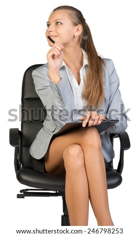 Businesswoman sitting on office chair with pen at her chin and clipboard on her knees, her head half-turned to her right, smiling. Isolated over white background