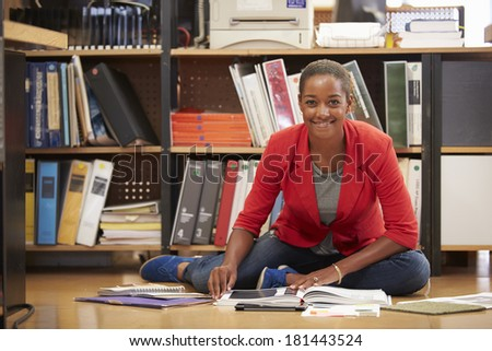 Businesswoman Sitting On Office Floor Reading Documents