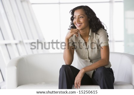 Businesswoman sitting on sofa in lobby in office - stock photo
