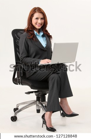 businesswoman sitting on the office chair holding a laptop