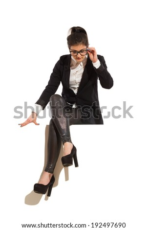 Businesswoman sitting on top of the banner. Young elegance woman sitting on a banner, holding glasses and reading. Full length studio shot isolated on white.