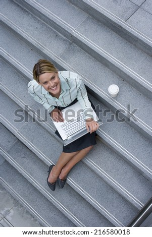 Businesswoman sitting on urban stairs with coffee and laptop - stock photo