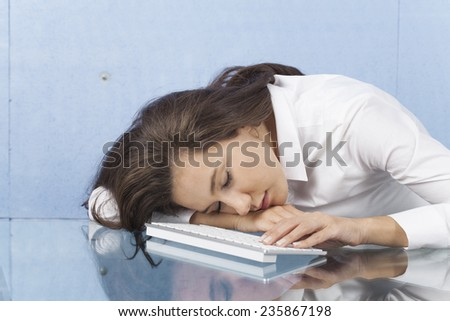 Businesswoman sleeping at workplace, her fingers touching keyboard - stock photo