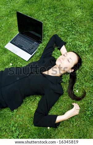 Businesswoman sleeping beside a laptop - stock photo