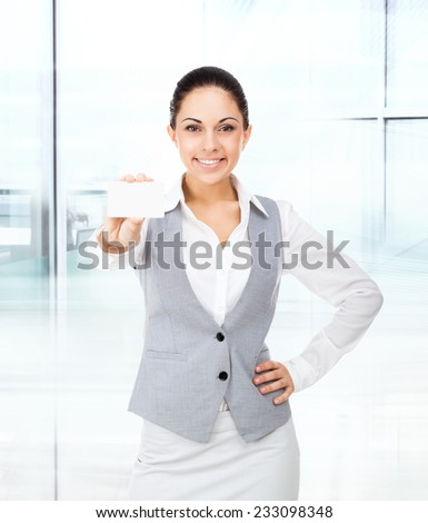 Businesswoman smile hold blank business card, young attractive business woman give visiting, credit card with empty copy space in modern office - stock photo