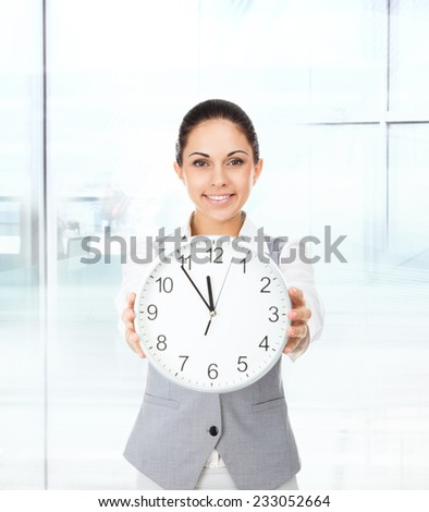 Businesswoman smile, hold clock, young attractive business woman in modern office - stock photo