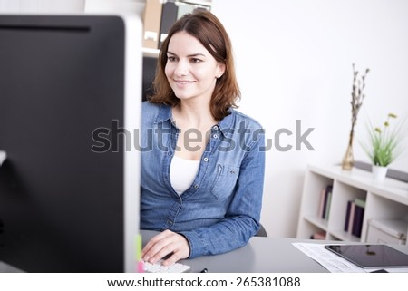 Businesswoman smiling as she works at her desktop while sitting at her desk, view past the edge of the monitor - stock photo