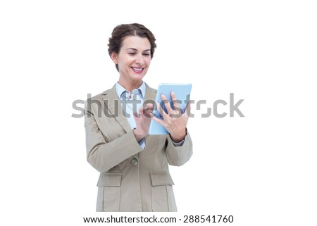 Businesswoman smiling while looking at a tablet against white bacground - stock photo