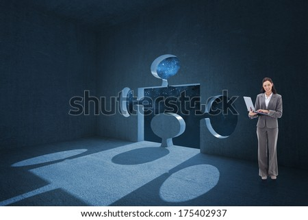 Businesswoman smiling with a laptop against jigsaw door in dark room
