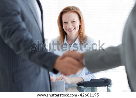 Businesswoman smiling with businessmen greeting each other in the foreground at a job interview - stock photo