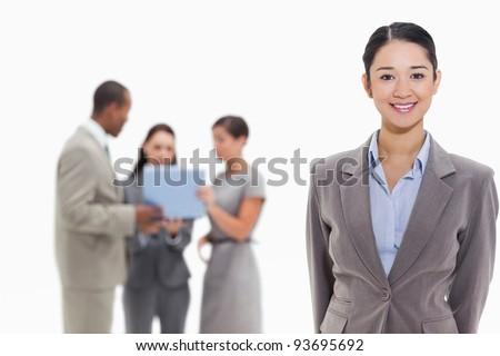 Businesswoman smiling with co-workers watching a laptop in the background