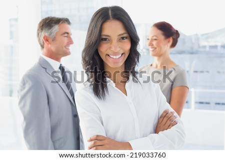 Businesswoman smiling with folded arms at work - stock photo