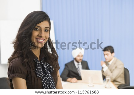 Businesswoman smiling with her colleagues in the background