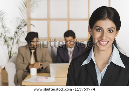 Businesswoman smiling with her colleagues in the background - stock photo