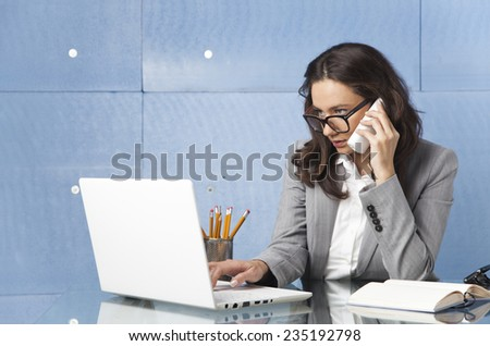 Businesswoman speaking on the phone while typing on keyboard and looking at laptop - stock photo