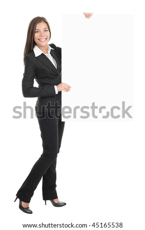 Businesswoman standing and holding a white empty billboard or signboard in full length. Beautiful mixed race chinese / caucasian woman isolated on white background.