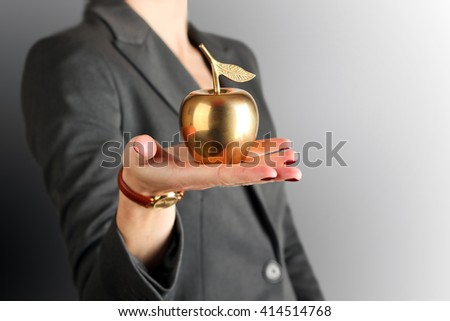 Businesswoman standing and holding golden apple in her hand. - stock photo