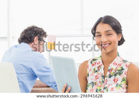 Businesswoman standing and using tablet with colleague behind her - stock photo