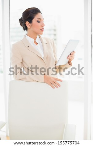 Businesswoman standing behind her chair holding tablet pc in her office