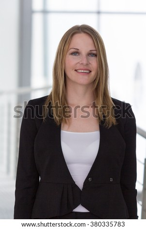 Businesswoman standing in a modern Building with a white shirt and black pants