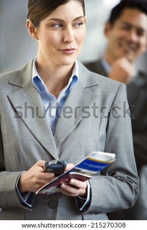 Businesswoman standing in airport terminal, holding mobile phone and ticket, making sideways glance - stock photo