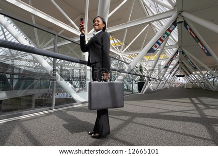 Businesswoman standing in an office atrium smiling as she takes a picture on her cellphone. Lobby has international flags adorning it. Horizontally framed shot.
