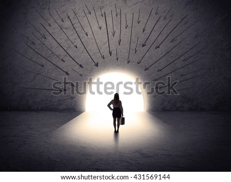 businesswoman standing in front of the huge gate with drawn arrows pointing to the entrance - stock photo