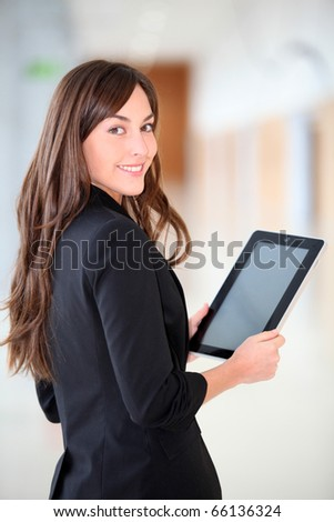 Businesswoman standing in hall with electronic pad - stock photo