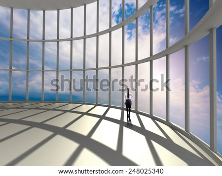 businesswoman standing in office and looking at sky in window - stock photo