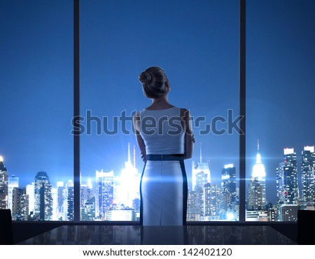 businesswoman standing in office and looking in night city - stock photo