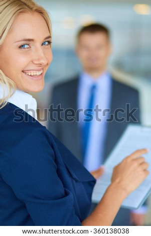 Businesswoman standing in office , holding documents in hand