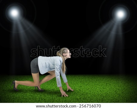 Businesswoman standing in running start pose at green grass court illuminated by two spotlights, looking ahead, smiling - stock photo