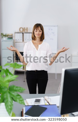 Businesswoman standing meditating in her office with her eyes closed and a tranquil expression on her face - stock photo