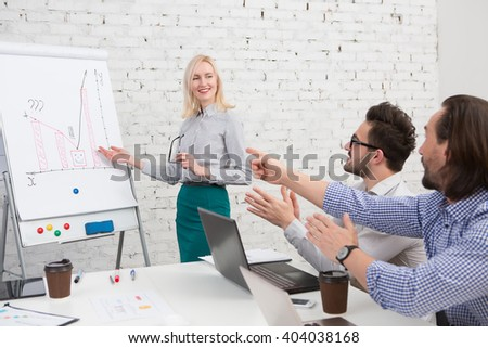 Businesswoman standing near whiteboard and reporting for audience. Happy blonde showing shemes to her business colleagues men. - stock photo