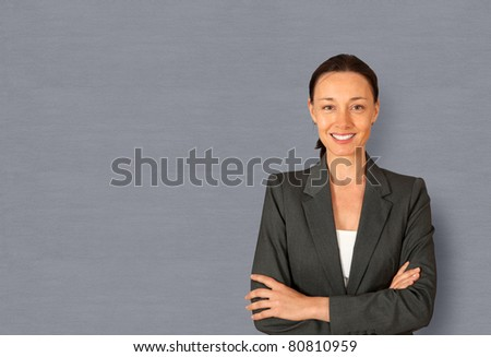 Businesswoman standing on grey background with arms crossed - stock photo