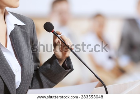 Businesswoman standing on stage and reporting for audience - stock photo