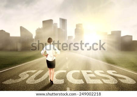 Businesswoman standing on the highway to new city, symbolizing as the way to the new success - stock photo