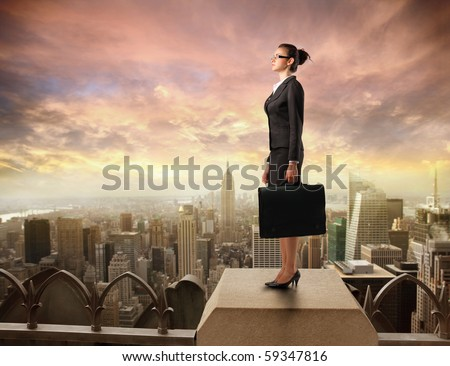 Businesswoman standing on the rooftop of a skyscraper - stock photo