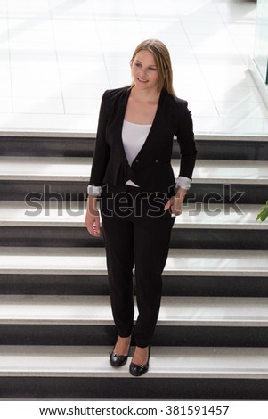 Businesswoman standing on top of a staircase