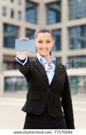 businesswoman standing outdoor and showing business card