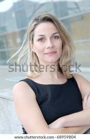 Businesswoman standing outside with arms crossed - stock photo
