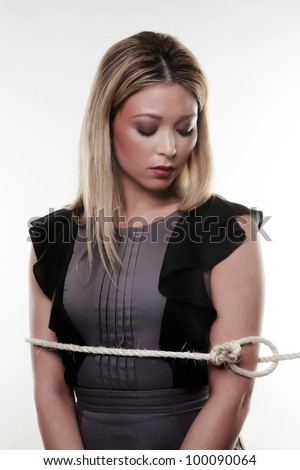 businesswoman standing with a rope lasso around her not looking to happy at being capture - stock photo