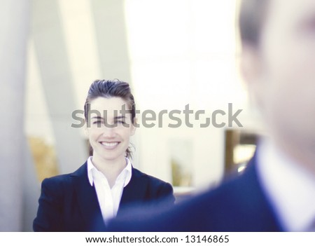 businesswoman standing with arms crossed directly behind businessman
