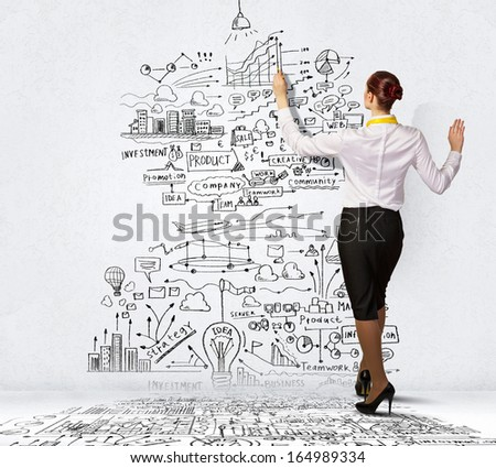 Businesswoman standing with back drawing business ideas on wall - stock photo