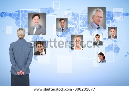 Businesswoman standing with hands behind back against background with world map
