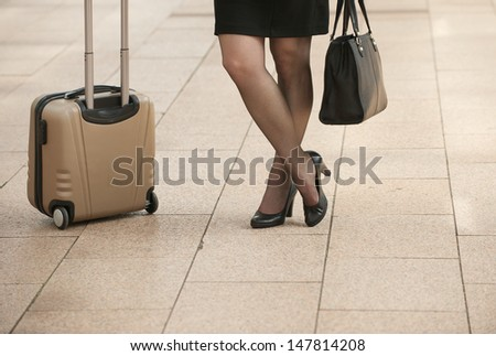 Businesswoman standing with travel bags on city sidewalk - low angle