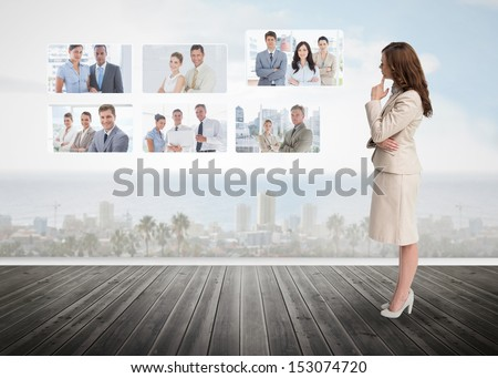 Businesswoman staring at futuristic interface showing partners - stock photo